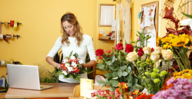 Portrait of mature florist holding a bouquet of flowers in flower shop. Online shopping.