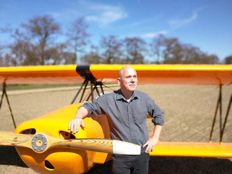 Man standing next to small plane