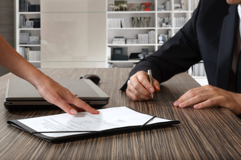 female hand pointing to businessman at signature place on a contract document