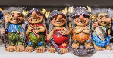 figurine statues of trolls with viking helmets on