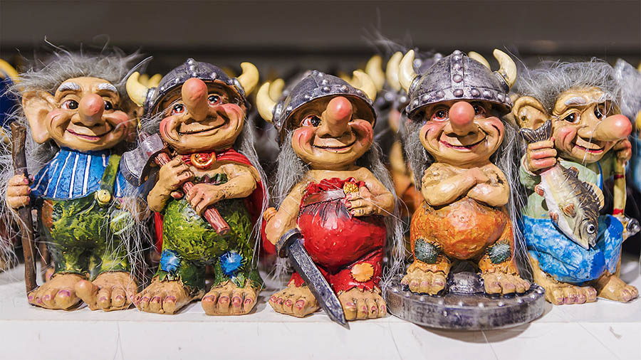 figurine statues of trolls with viking helmets on