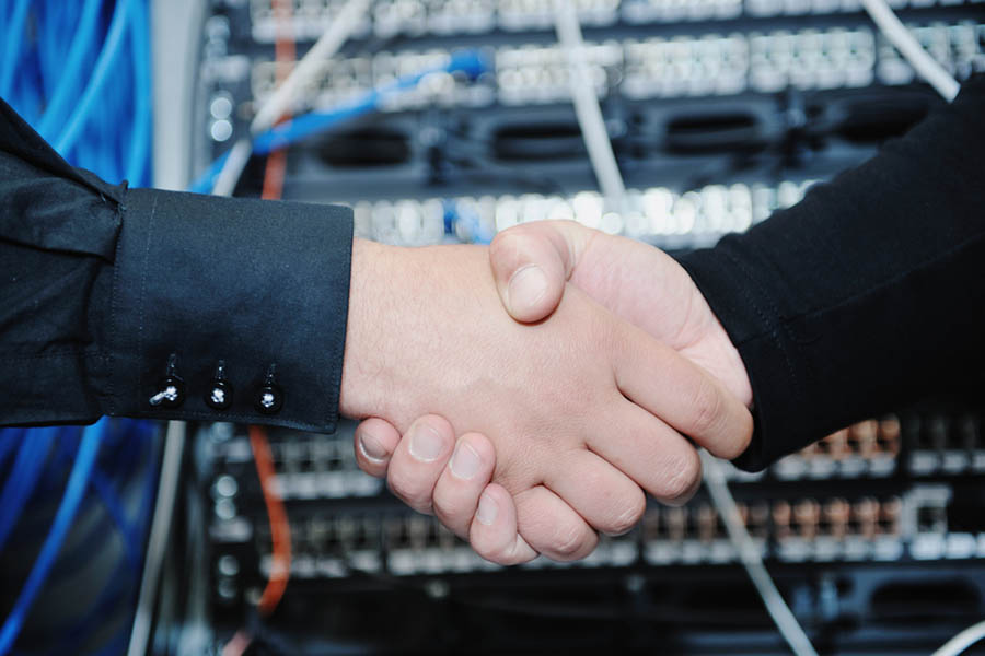 two people shaking hands in front of server with plugs
