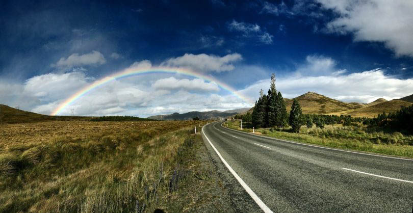 highway road leading to horizon clouds in blue sky with rainbow