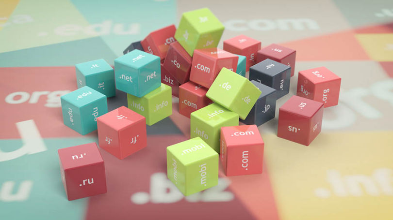 stock image: multiple dice in a cluster with tld examples on each side: '.com' '.net' '.us' '.org' etc
