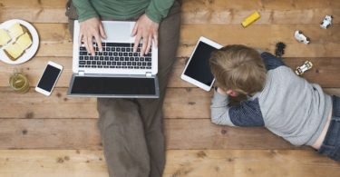image of parent with laptop and child next to them with ipad